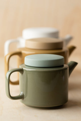 Three Teapots lined up in a row with ply wood background