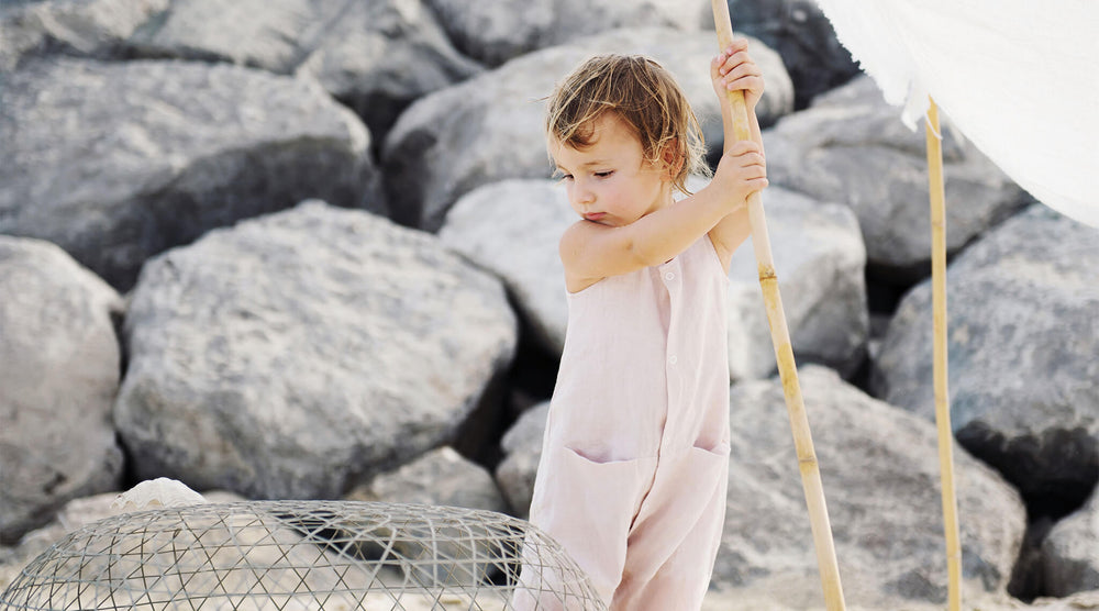 Little girl is on the beach, wearing pink linen baby baby romper.