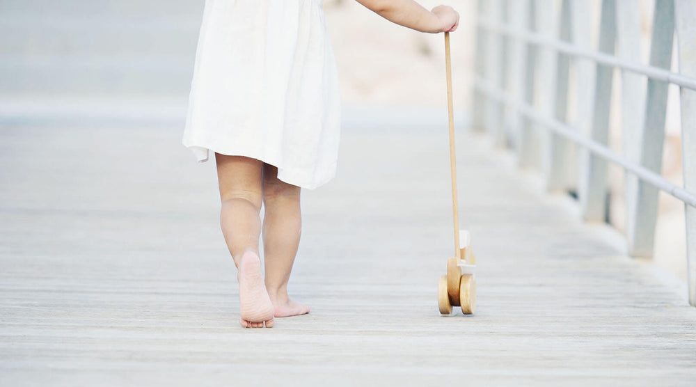Little girl wearing white linen dress is walking with wooden push toy.