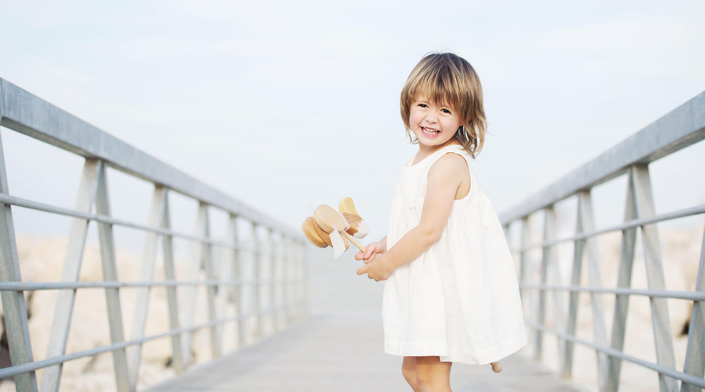 Little girl is on the jetty, wearing white linen dress and holding natural wooden toy. Smiling.