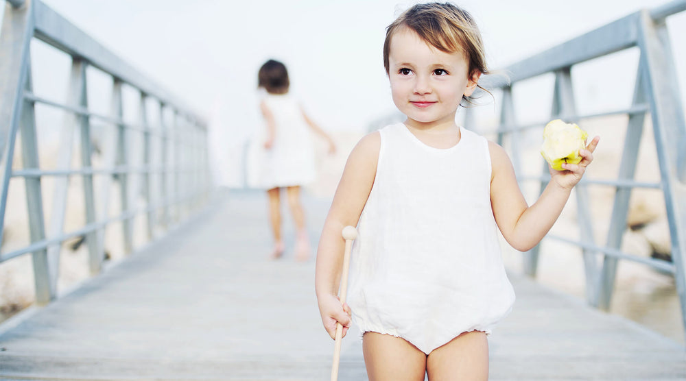 Baby girl is standing on the jetty wearing white linen romper, eating an apple, smiling.