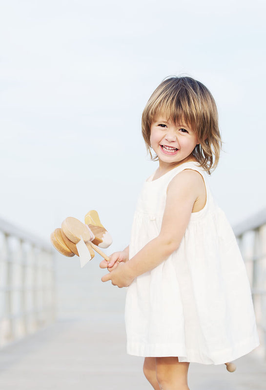 Little girl is wearing white linen dress, holding wooden toy, smiling.