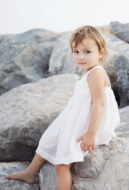Little girl is sitting on the rock at the beach wearing white linen dress.