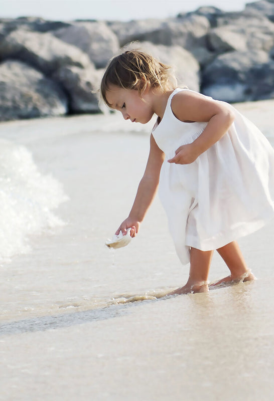 Little girl, wearing white linen dress, is putting a shell into the water at the beach.