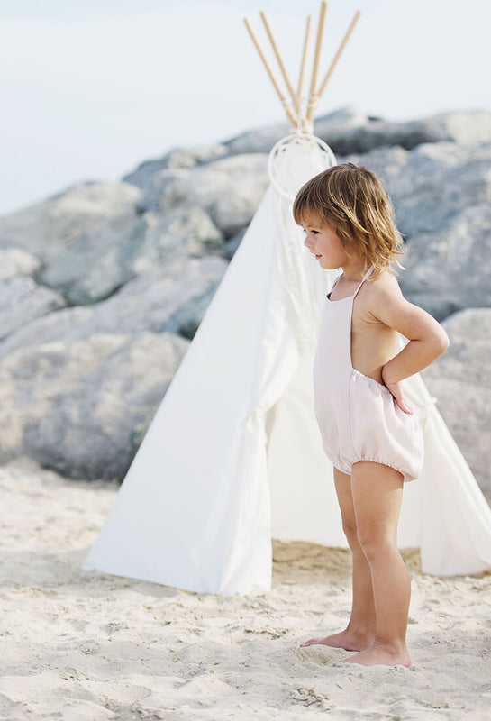 Little girl is standing on the beach sand, wearing backless pink linen romper.