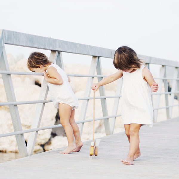 Two little girls, wearing white linen dress and white linen romper are on the jetty at the beach, playing with natural wooden push toy.
