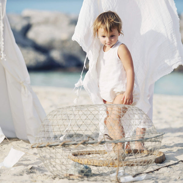 Babygirl wearing white linen sleeveless bubble romper is on the beach on the sunny summer day.