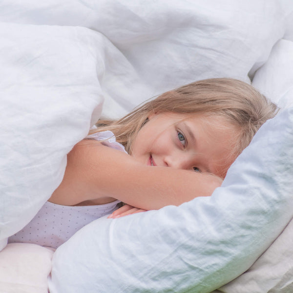 Young girl is laying on the linen bedding: white duvet cover, pink fitted sheet, white pillow case; smiling.