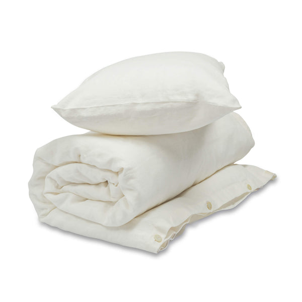 White linen baby, kids bedding set. Rolled up Duvet is in duvet cover with pillow in pillow case on top.
