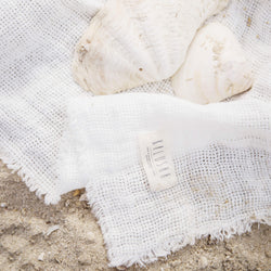 White linen baby and kids blanket with the cotton tag of Kalusha logo. is on the beach sand.