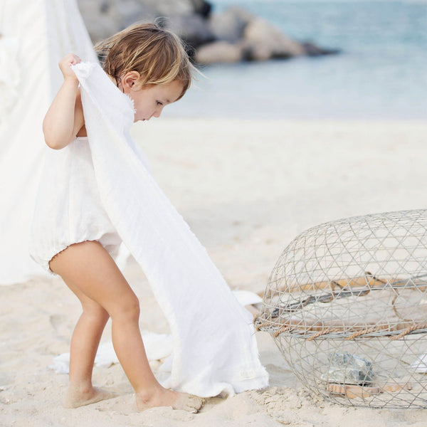 Baby girl is on the beach holding white linen baby and kids blanket.