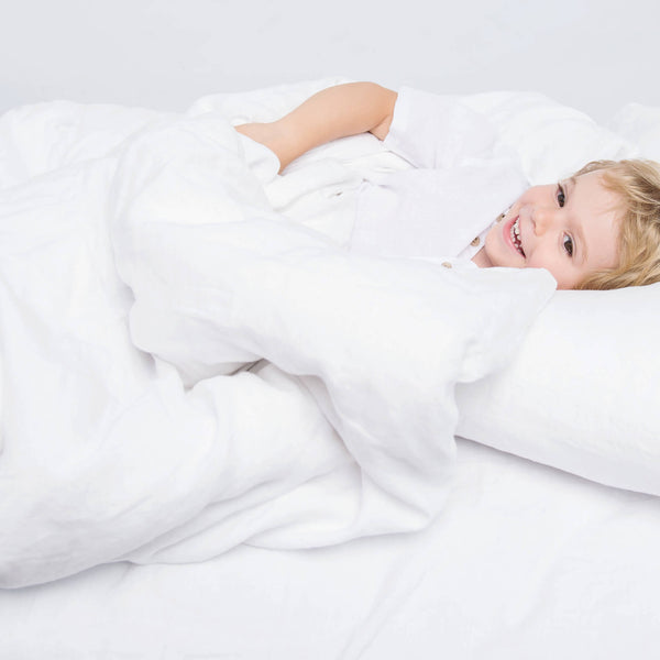 Babyboy is laying on the bed made with white linen bedding set, smiling. Kids linen bedding.