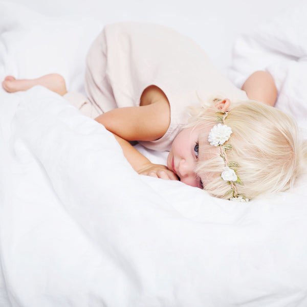 Baby girl, wearing pink linen sleeveless romper is laying on the white linen duvet cover.