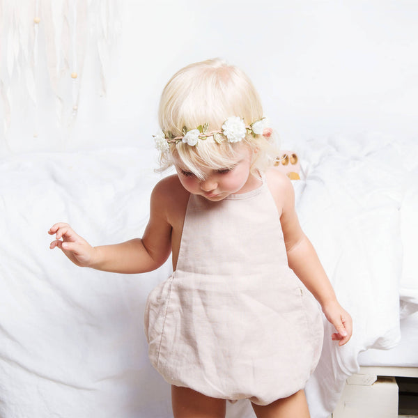 Baby girl is wearing pink linen backless romper. Bubble romper with soft elastic gathers for legs and snaps for leg opening.