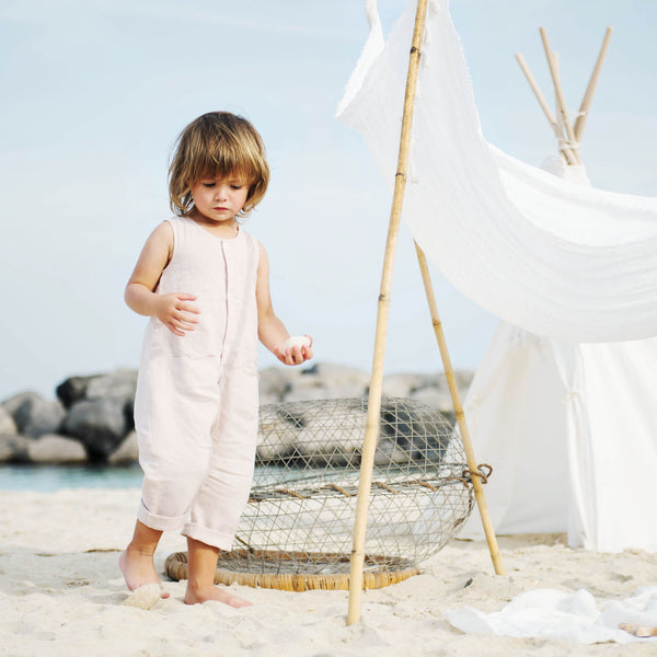 Baby girl is on the sunny beach wearing pink linen oversized romper with rolled up hems, snap opening at the front and 2 front inseam pockets.