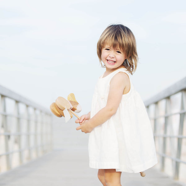 Babygirl in white linen dress is standing on the jetty, holding goose wooden push toy; smiling.