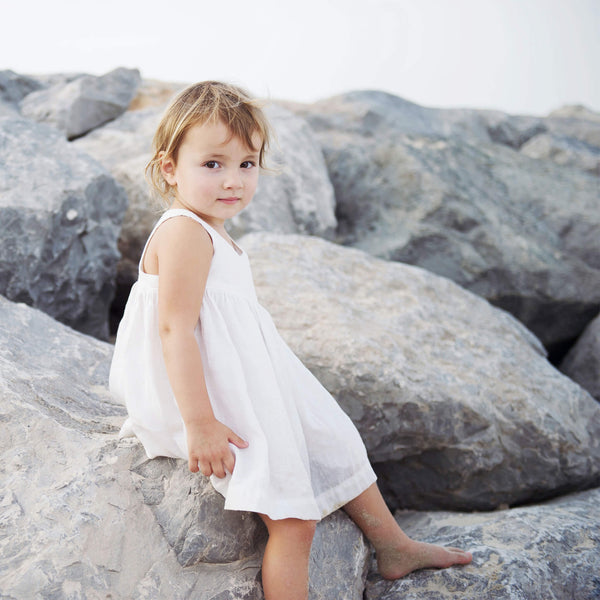 Babygirl is sitting on the rocks at the beach, wearing white sleeveless linen dress with gathers at the waist.