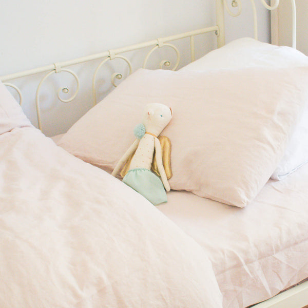 Pink bedding set with soft toy on the pink linen pillowcase.