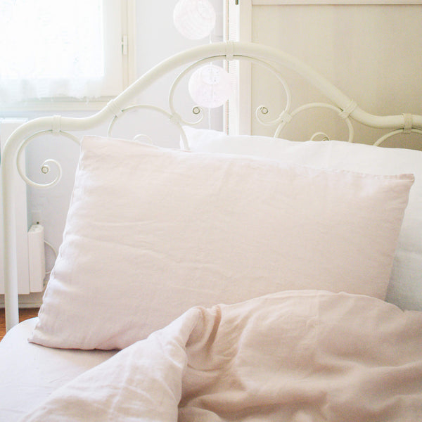 Pink linen bedding set of duvet cover, fitted sheet and pillow case on white iron bed.