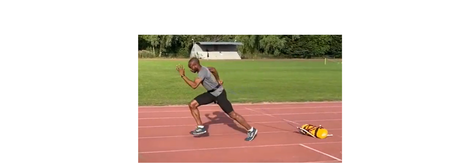 Athlete practicing acceleration drills with a power sledge resistance harness