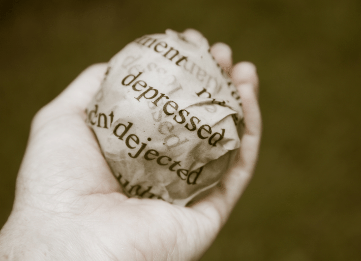 Mental health in sport: Athlete holding a ball of paper with depression