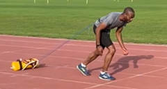 Athlete starting to sprint pulling a weighted resistance power sled for acceleration training
