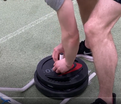 Athletes loading weights on a resistance power sled