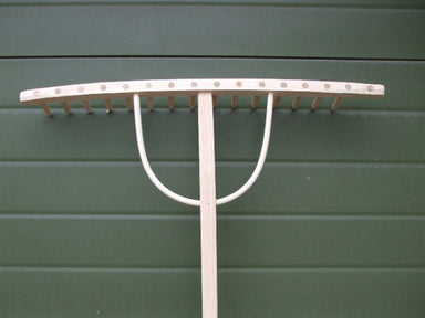 Wooden rake with a wide rectangular head and straight teeth