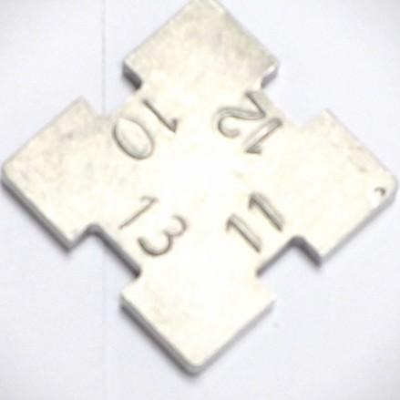 Pocket sized square metal plate with different sized grooves in each side to measure the thickness of the rim of a discus