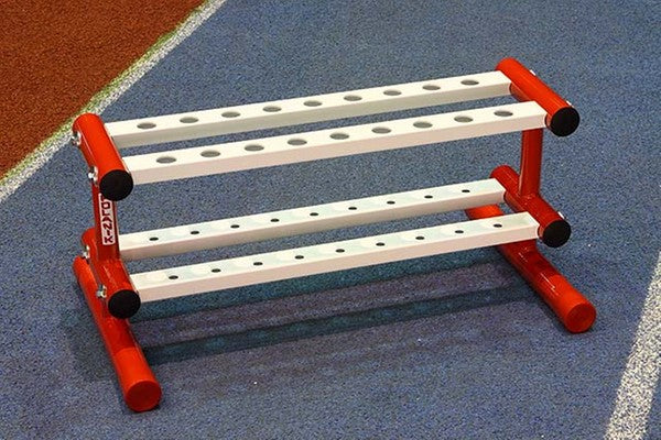 Red and white painted stand with 18 holes on lower and upper levels to hold javelins when not in use.   Includes a galvanised handle and wheels to allow the trolley to be stored away from the throwing area.