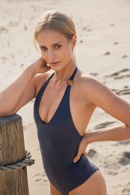 Radiate your optimum self in our dazzling MILA one-piece swimsuit. We are artfully crafted to illuminate all skin tones this elegant V-neck accented by the signature Sense Swim ® golden hardware in the front. Comes with an adjustable neck tie that gracefully dips like the setting sun to a lower back. Complete with full lining, this seamless style generates an immaculate fit in our body sculpting and fast-drying three-dimensional fabric.