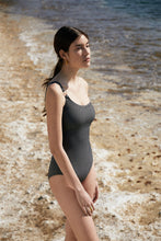 Load image into Gallery viewer, Awaken your senses in our most loved maillot. The PUJA one-piece swimsuit breezes across the body in an asymmetrical cut accented by the signature Sense Swim ® golden hardware in the front. While our unique concealed silicone elastic firmly caresses the figure and décolletage along with an adjustable strap.