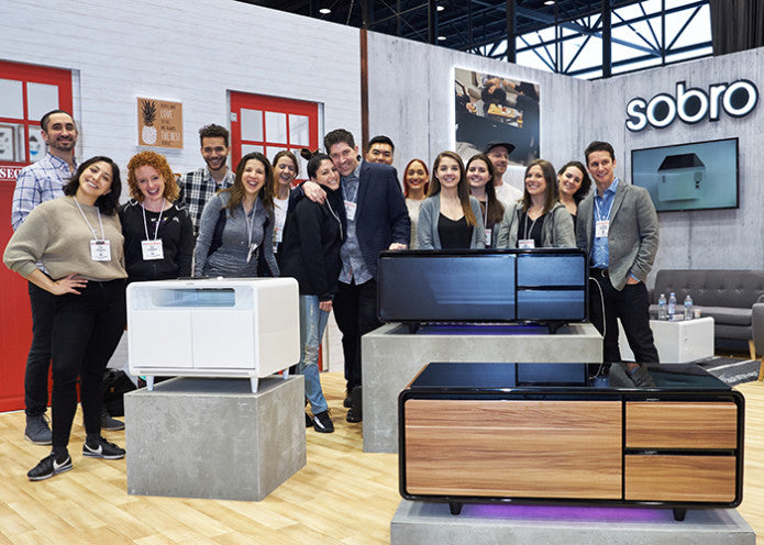 Group photo of Sobro team standing around displays of Sobro tables