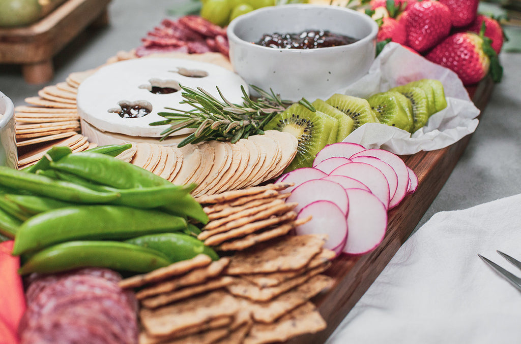 Easter charcuterie spread of snap peas, crackers, brie, and fig jam on a wood serving board from Siroh & Ivy