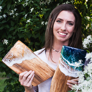 Siroh & Ivy artist Sarah Cunzolo smiling and holding a sea foam serving board and an ocean serving board
