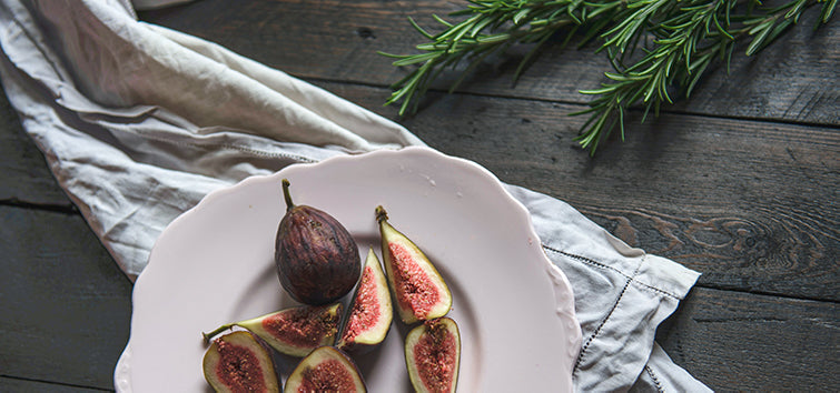 Fresh figs cut open and spread on a white porcelain plate with a white napkin and rosemary sprigs on a grey wood table