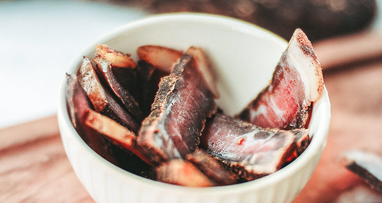 Cured and dried slivers of meat placed inside a white porcelain ramekin on a wood table