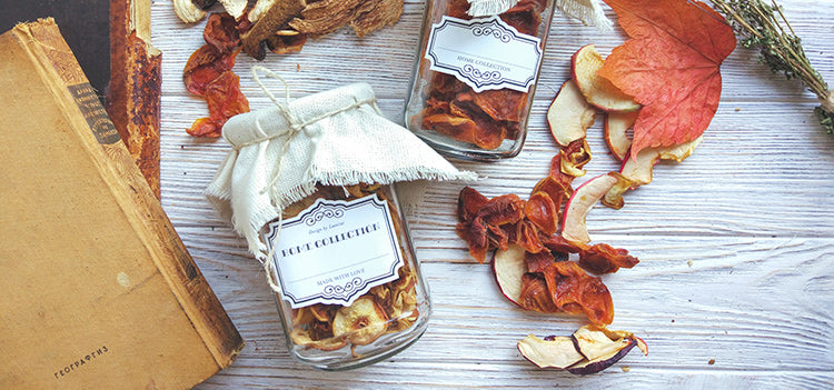 Dried apples stored inside mason jars that are arranged on a white wooden table with orange leaves