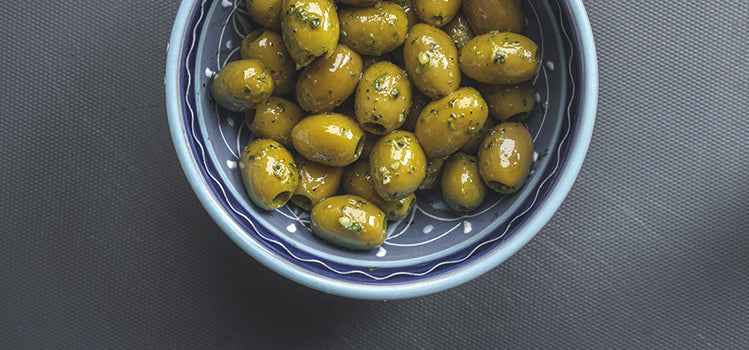 Green olives covered with oil and spices sitting inside of a blue china bowl