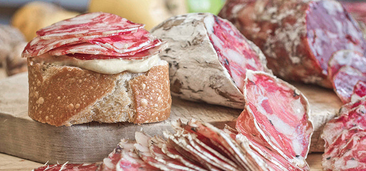 Italian soppressata sliced thin and piled high on a sliver of french baguette on a wood serving board