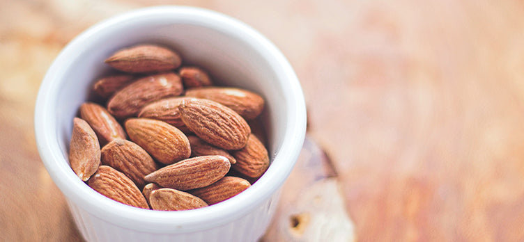 Light brown toasted almonds sitting inside a white porcelain ramekin on a wood serving board