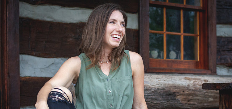 Sarah Cunzolo owner of Siroh & Ivy sitting on porch of log cabin in a green tank top smiling