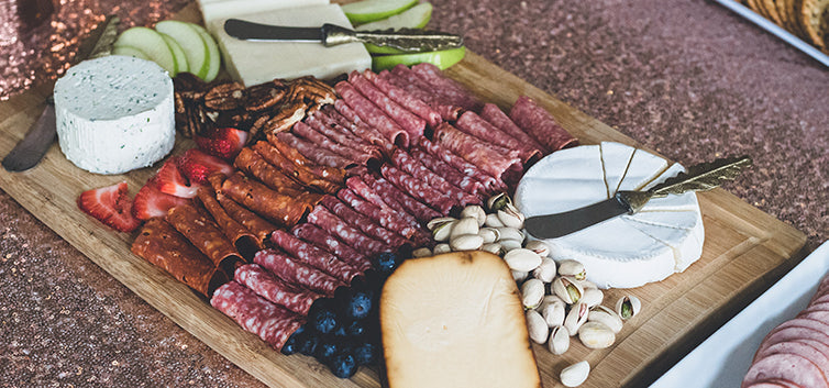 Complete charcuterie arrangement on a wood serving board with brie, salami, and granny smith apples