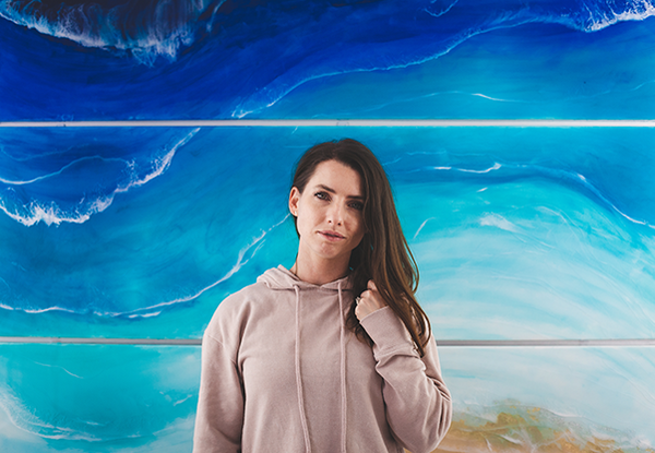Sarah Cunzolo, artist of Siroh & Ivy, stands in front of a large blue ocean resin painting staring with a soft expression