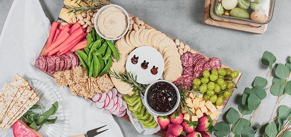 Easter themed charcuterie spread with brie, fig jam, grapes, strawberries, and hummus on a wood serving board from Siroh & Ivy