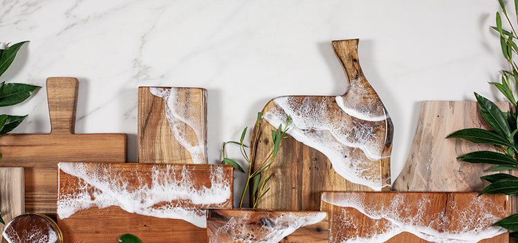 Large collection of handmade wood serving boards from Siroh & Ivy arranged on a marble countertop with sea foam inspired resin painting