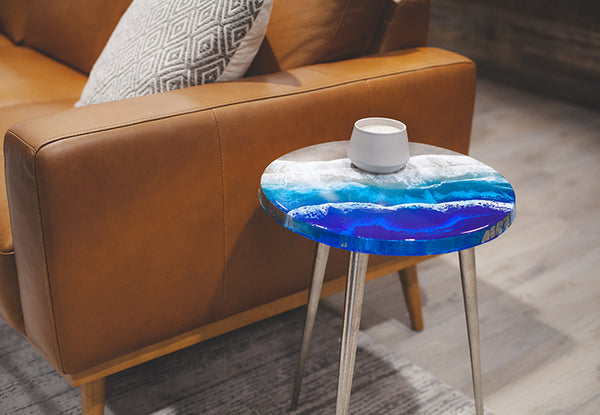 Inlet is an original work of resin art by Siroh & Ivy on a metal side table that mimics an ocean wave with deep and light blues and white foam lacing throughout