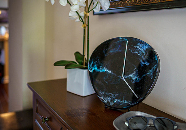 Spacedial is an original piece of resin art from Siroh & Ivy on a functional clock that mimics the depths of space and a nebula with deep blacks, shiny glitter, and swirls of green, blue, and white