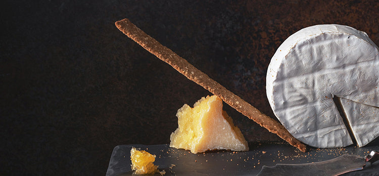 An uncut wheel of brie cheese sitting on a piece of dark slate with a thin crispy breadstick