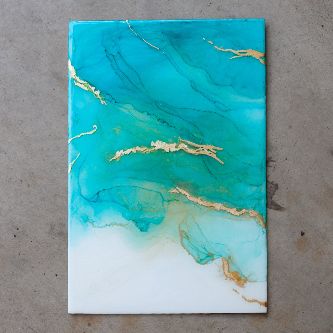 Serenity is an original piece of fine art from Siroh & Ivy that features resin mixed with hues of aqua blue alcohol inks and touches of gold leaf